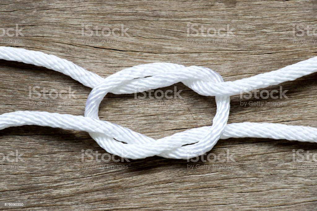 White rope in reef knot shape on wood background stock photo