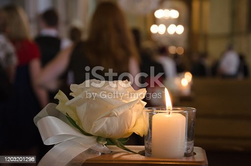 A white rose and a white candle as weddin arrangement in a church