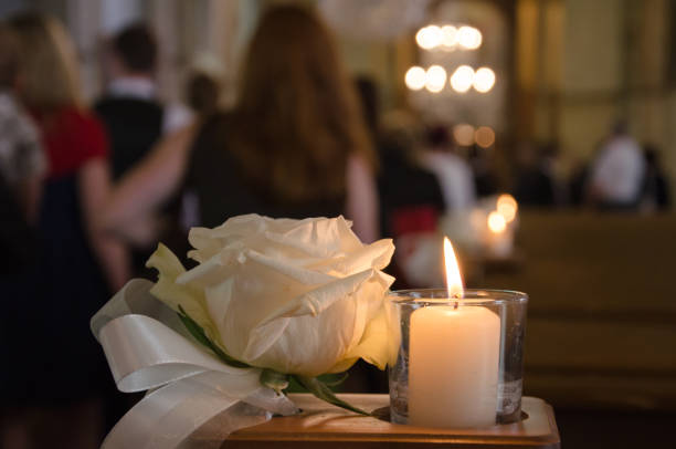 rosa bianca e candela in una chiesa - funerale foto e immagini stock