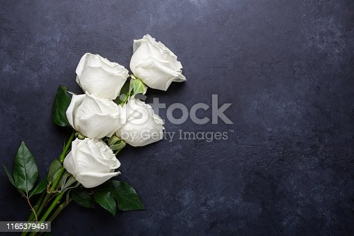 White rose flowers bouquet on black stone background Valentine's day greeting card Copy space Flat lay