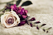 White rose next to purple flowers over a calligraphy cloth