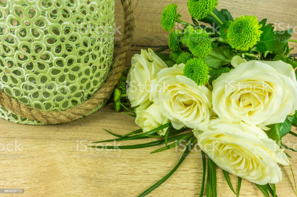 White roses in a green vase on a rustic wooden table foto stock royalty-free