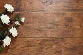 istock White roses on rustic wood background 674659818
