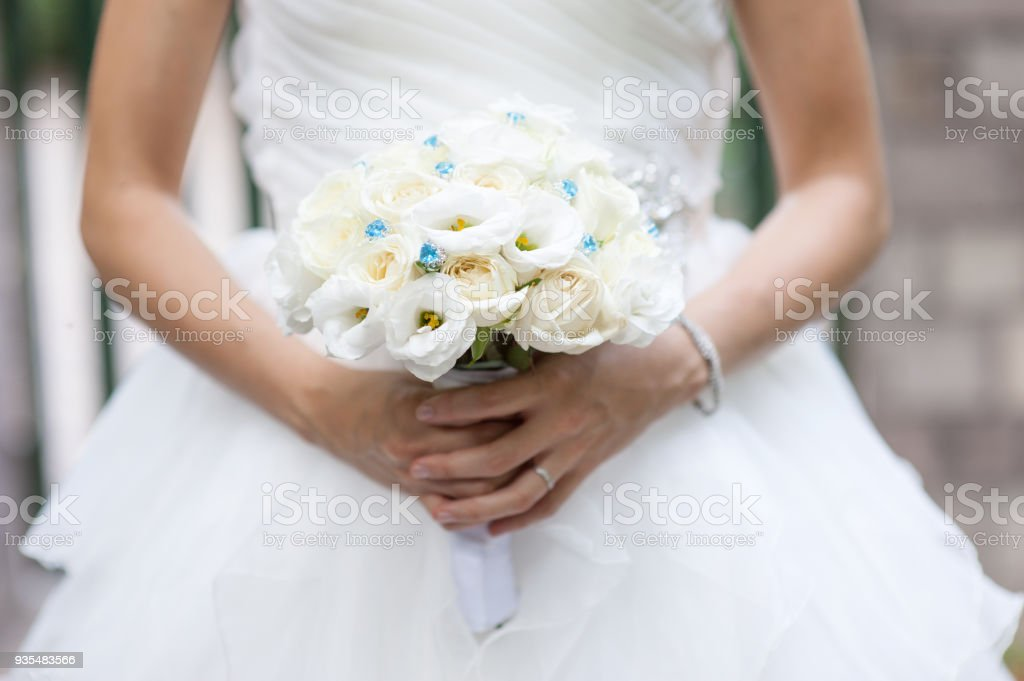 White roses wedding bouquet in bride's hand