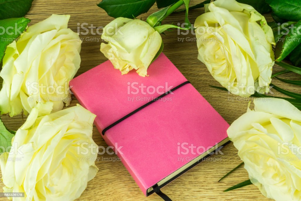White roses with a notebook on a wooden table ロイヤリティフリーストックフォト