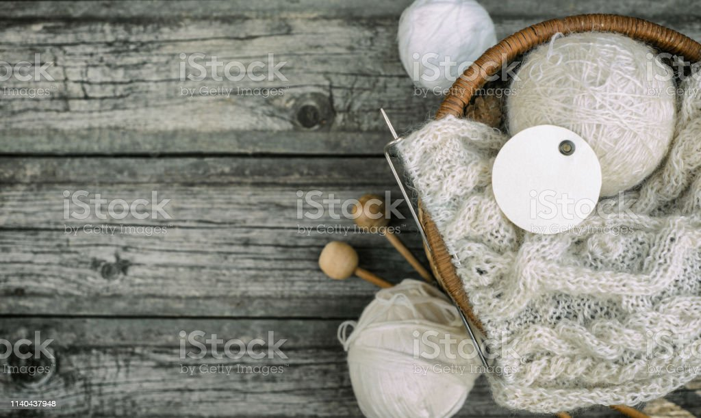 White round label on wool threads roll to basket with knitting and...