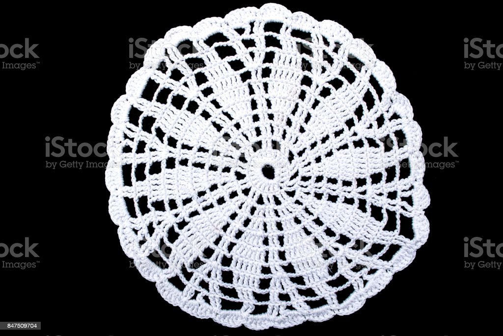 White round lace tablecloth isolated on black background, close up stock photo