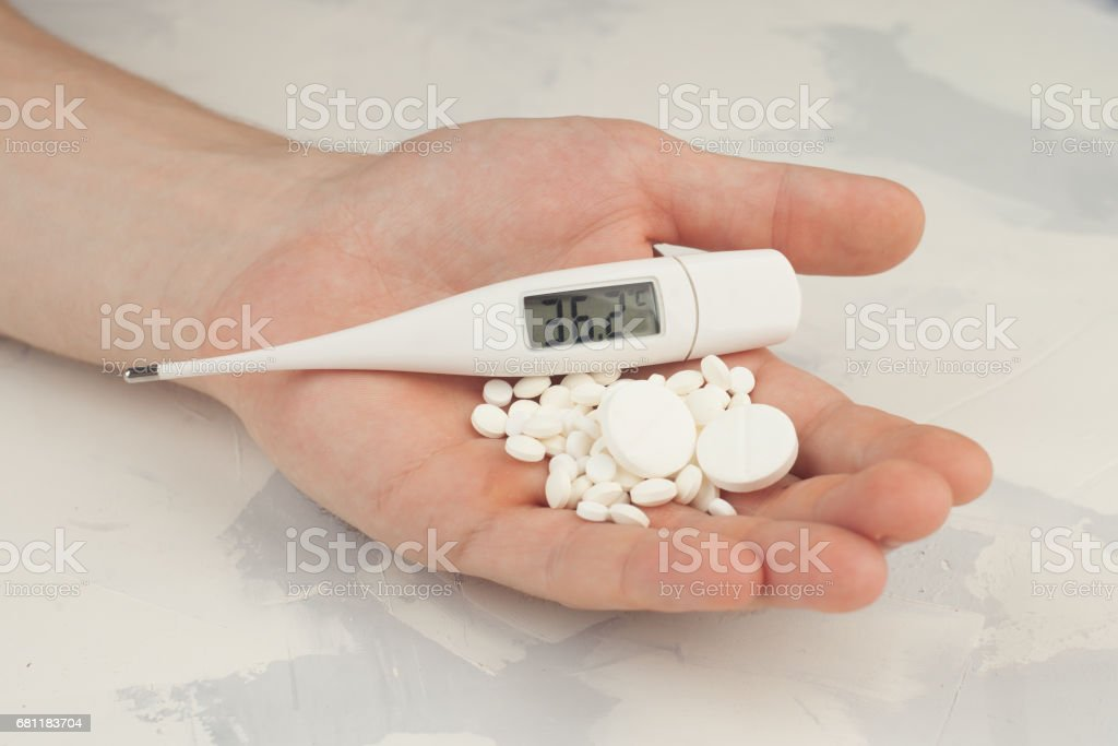 white round pills and thermometer on hand royalty-free stock photo