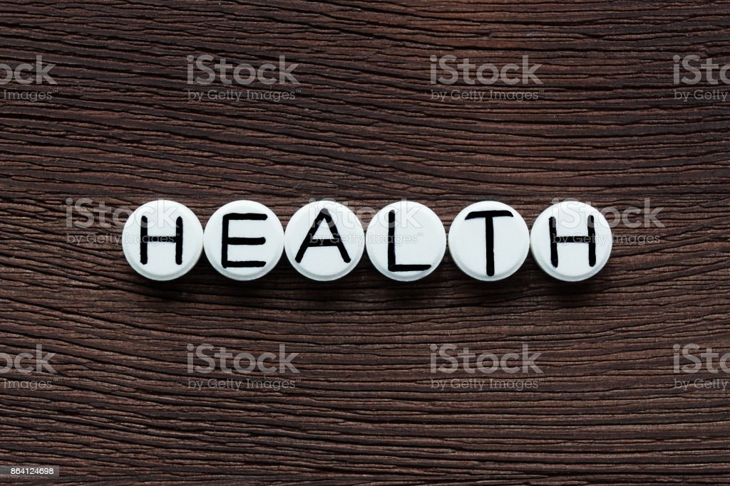 White round pills with inscription HEALTH on brown wooden board background royalty-free stock photo