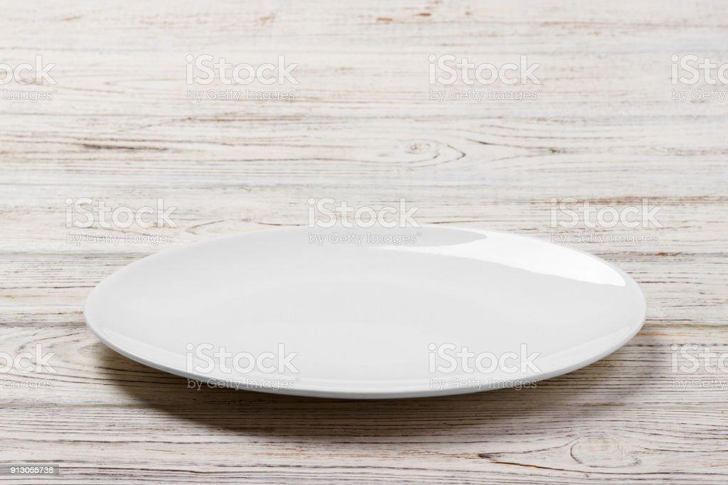 Plaque ronde de blanc sur fond blanc de table en bois. Vue en perspective - Photo