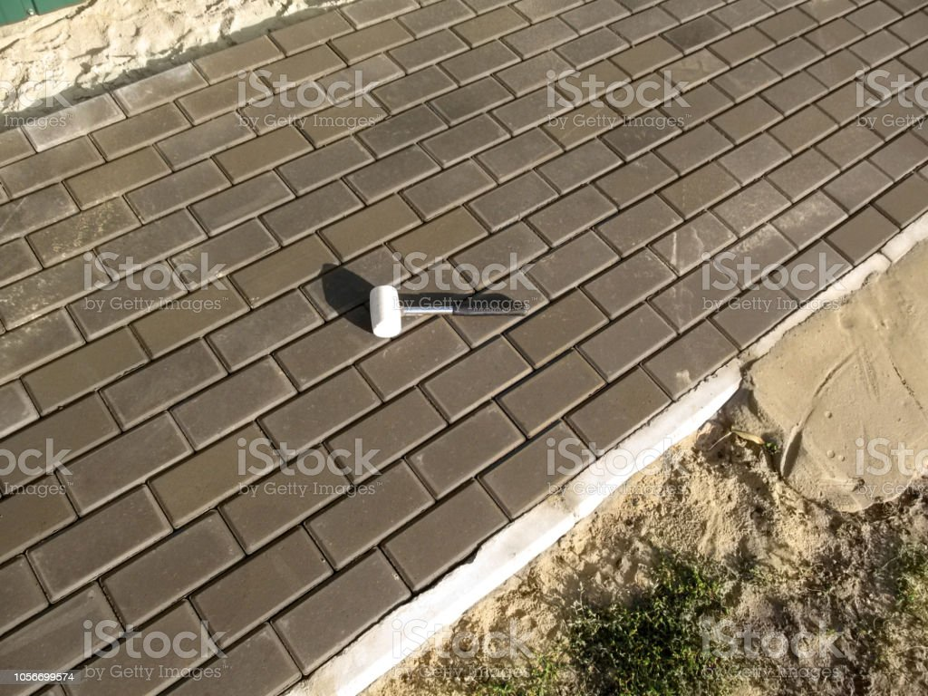 White rubber mallet lying on the gray surface of the new paving slabs stock photo
