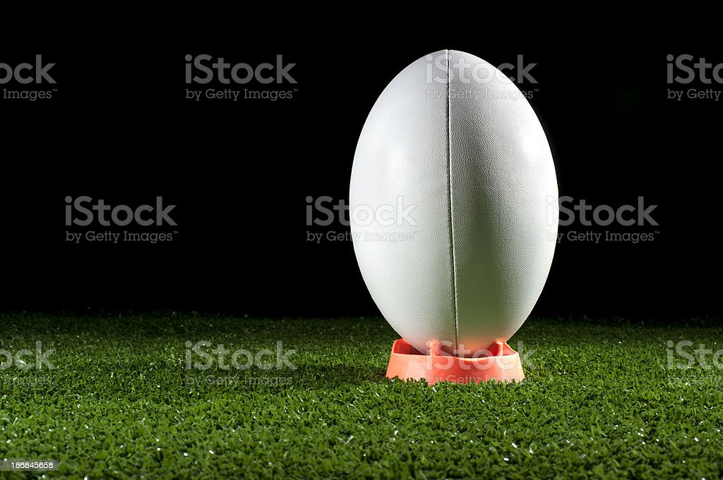White rugby ball on a tee in grass stock photo