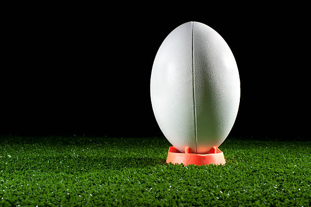 white rugby ball on a tee in grass - rugby ball stock photos and pictures
