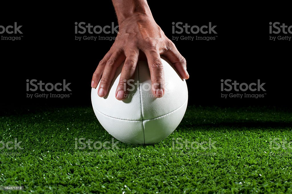 White rugby ball with hand holding it in grass stock photo