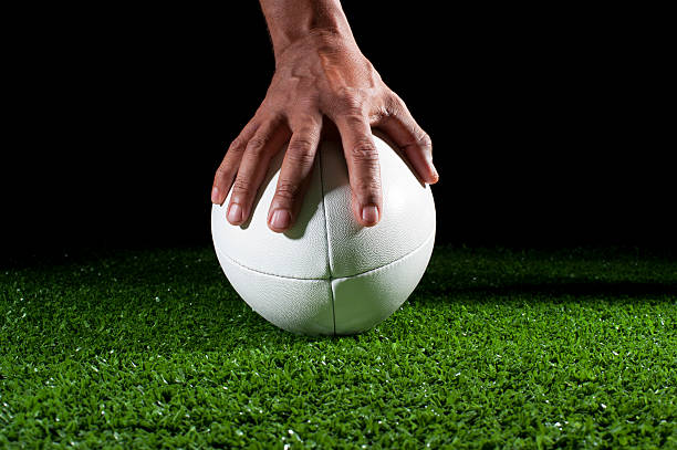 white rugby ball with hand holding it in grass - rugby ball stock photos and pictures