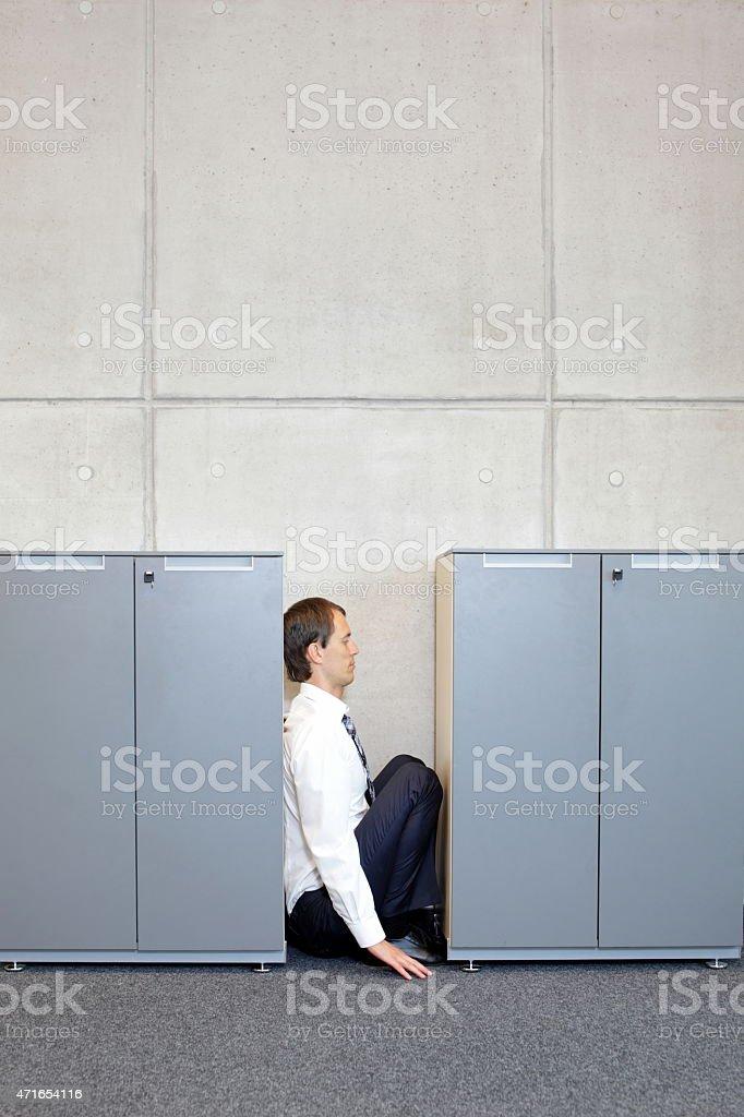 white sad business man crouching between cabinets stock photo
