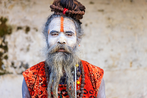 This Sadhu uses ashes of cremated remains to prepare specific white color of his makeup. In Hinduism, sadhu, or shadhu is a common term for a mystic, an ascetic, practitioner of yoga (yogi) and/or wandering monks. The sadhu is solely dedicated to achieving the fourth and final Hindu goal of life, moksha (liberation), through meditation and contemplation of Brahman. Sadhus often wear ochre-colored clothing, symbolizing renunciation.