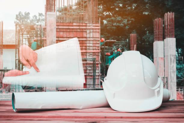 작업 건설 현장 주택 건물에서 나무 테이블에 흰색 안전 헬멧 및 종이 계획 청사진 및 손 엔지니어의 이중 노출 - double exposure 뉴스 사진 이미지