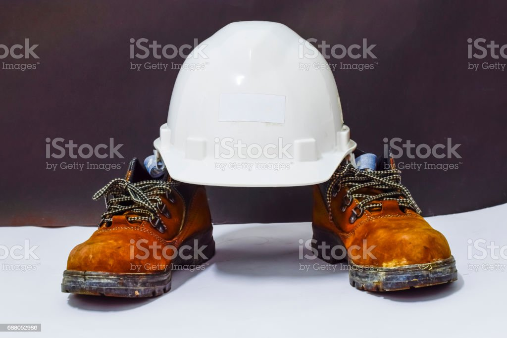 White safety helmet and safety shoes. This is Personal protective equipment for construction work. stock photo