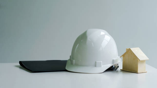 White Safety Helmet of workman house engineering worker put on table. stock photo
