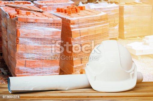 white safety helmet plastic, paper roll plan blueprint on wood floor table and pile brick orange background