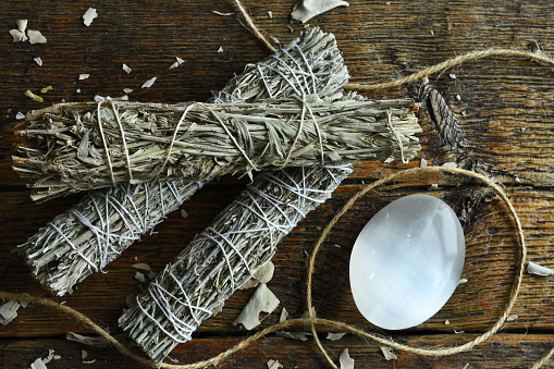 A close up image of several healing sage bundles and small selenite wand on a wooden table top.