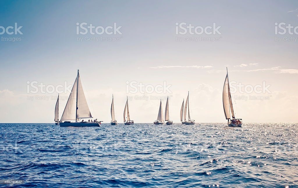 White sail sailing yachts close together in middle of ocean stock photo