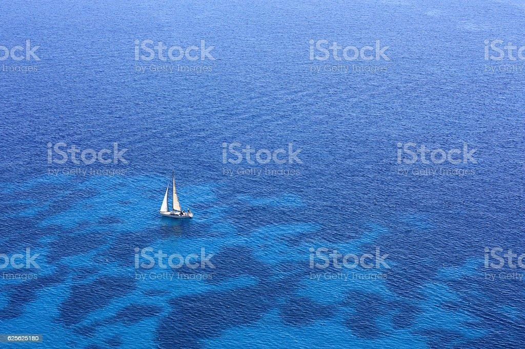 White sailboat in the blue sea. stock photo