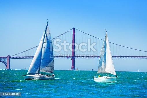 Beautiful seascape of San Francisco bay with white sailboats against Golden Gate Bridge, USA