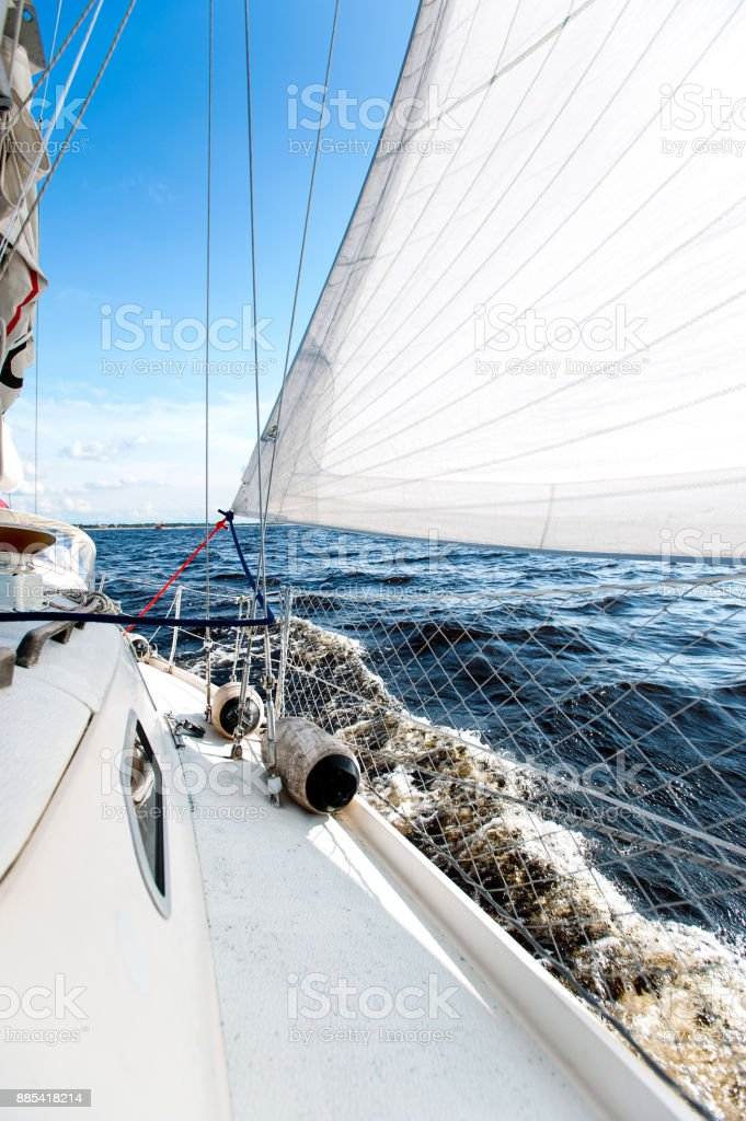 White sailing yacht at a speed swims to shore stock photo