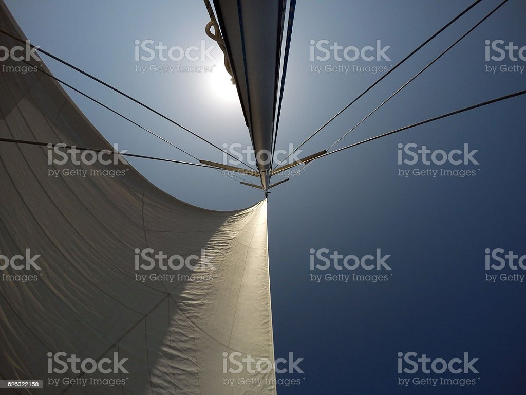 White sails and mast on blue sky stock photo