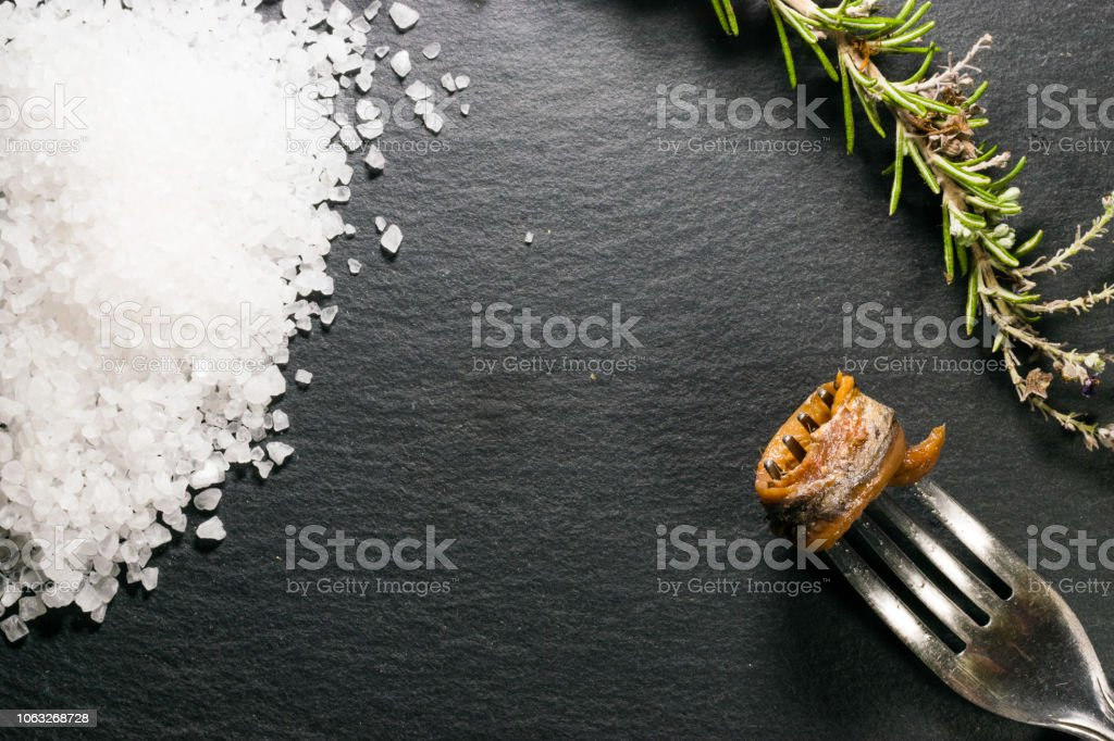 white salt and anchovies in oil and rosemary on a black slate top stock photo