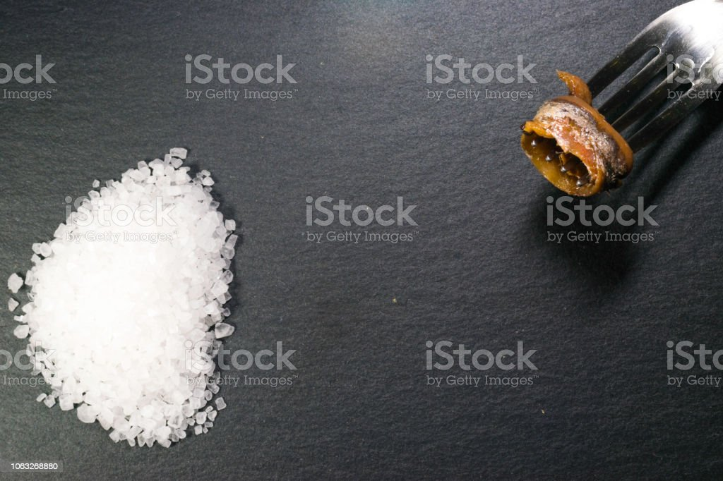 white salt and anchovies in oil on a black slate top stock photo