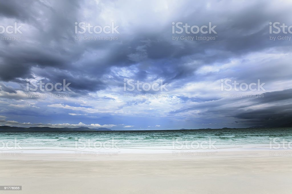 White sand beach on a dark cloudy day royalty-free stock photo