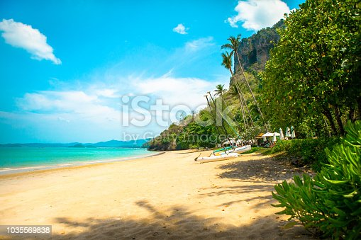 Beautiful white sand beach with kayak boats, palm trees and beautiful turquoise water. Sunshine and a blue sky.