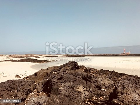 View of a beautiful beach in Fuerteventura with the lighthouse of El Tostón at the horizon