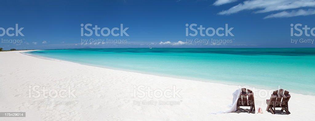 white sand beach with two adirondack chairs in Anegada, BVI stock photo