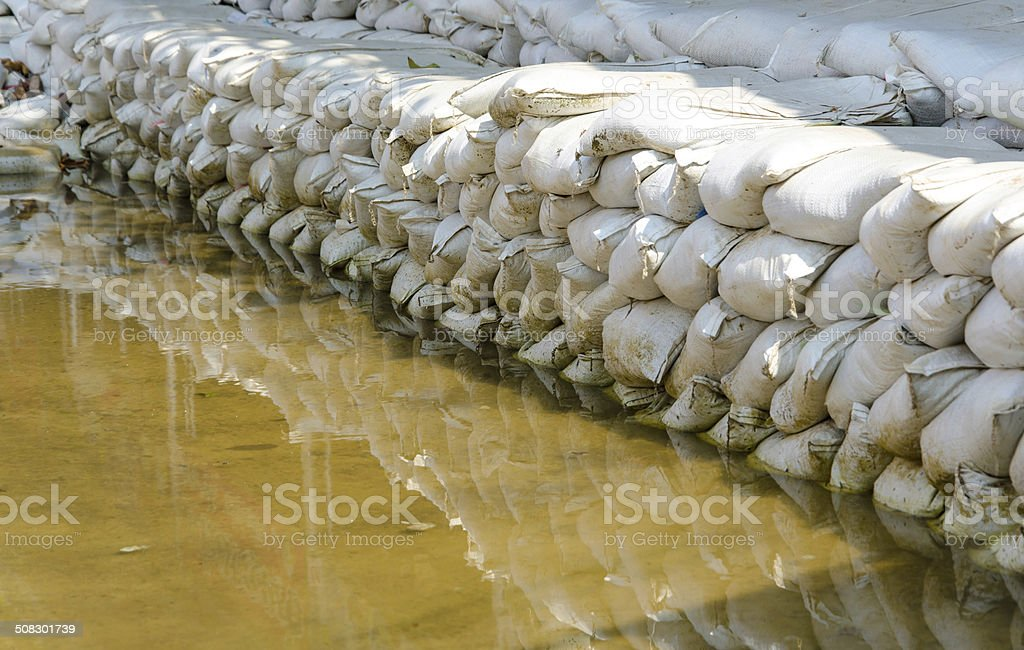 White sandbags for flood defense and it's reflection brown water stock photo