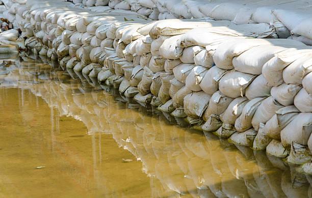 white sandsäcken für überschwemmung defense und seine spiegelung brown wasser - sandsäcke stock-fotos und bilder