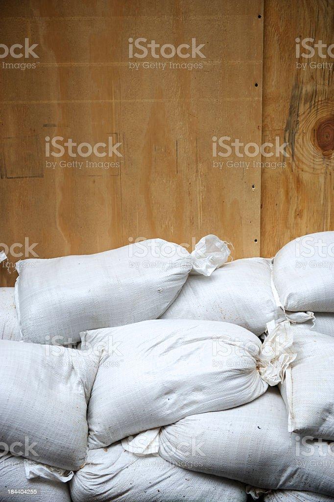White Sandbags Pile Up Against Plywood Protection stock photo