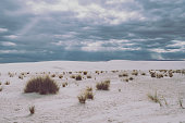 White Sands National Monument in New Mexico on overcast day with sunbeams coming from the sky