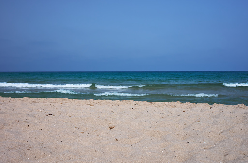 detail of a white sandy beach with a green sea and blue sky