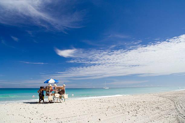 White sandy beach with a merchants cart and umbrella stock photo