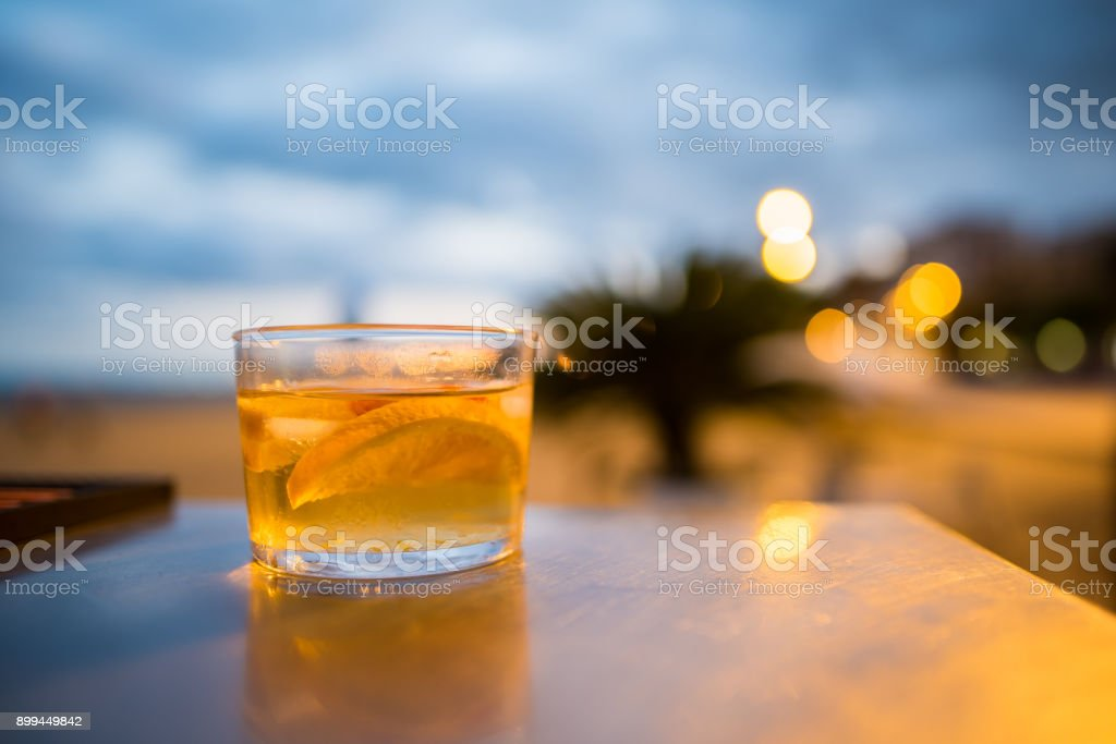 White Sangria in a glass at night at the beach stock photo