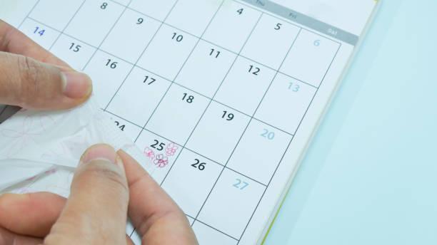 weiße damenbinde im kalender markieren. - bindewörter stock-fotos und bilder