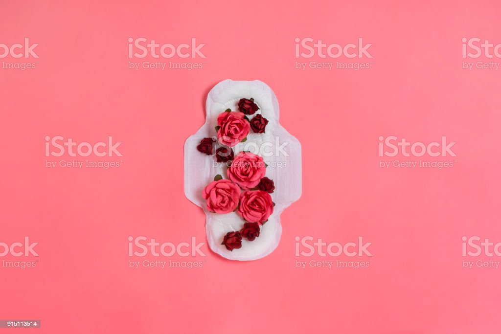 White sanitary pad with red and pink flowers on it, woman health or body positive concept. Pink background.  Flatlay. Copyspace stock photo