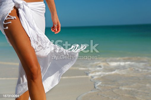 woman wearing a flowing white sarong on a beach