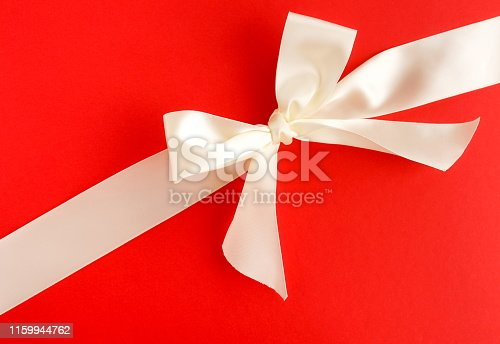 white satin ribbon on red background. top view. copy space