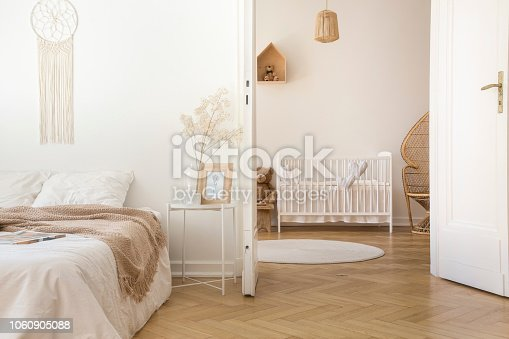 istock White scandinavian bedroom with door open to nursery with crib and toys, real photo 1060905088