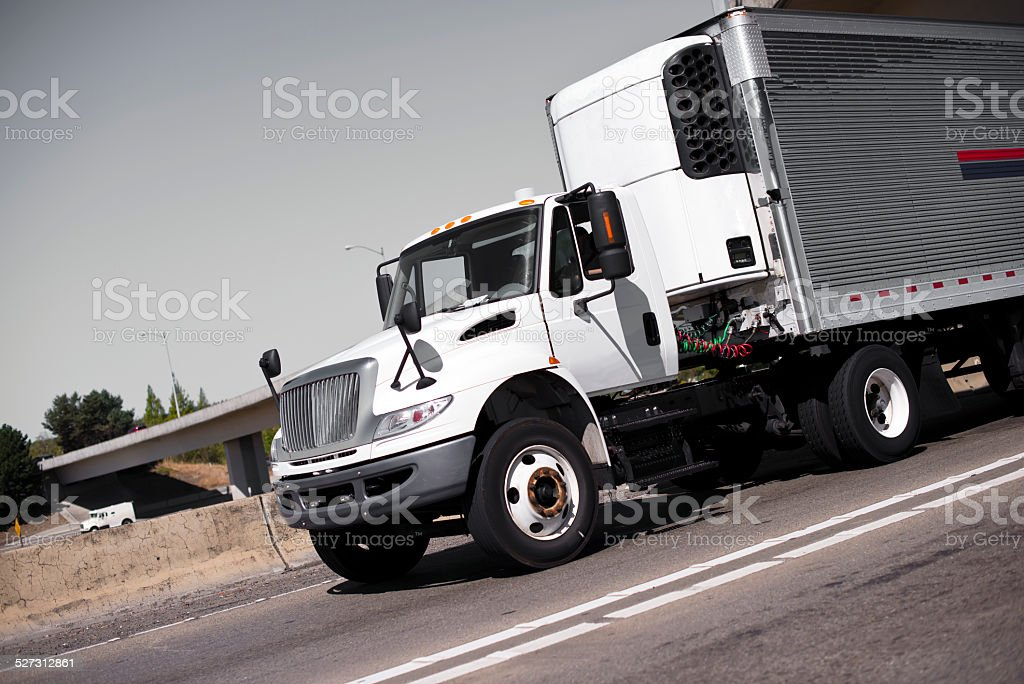 White semi truck and stainless steel refrigerator trailer on highway stock photo